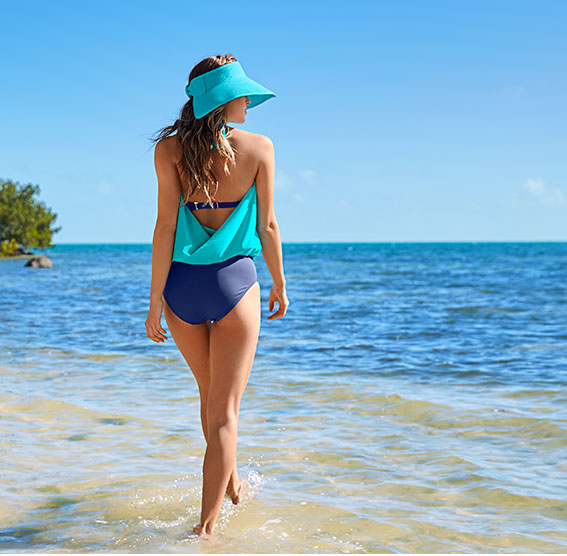 Girl walking on the beach wearing one-piece swimsuit.
