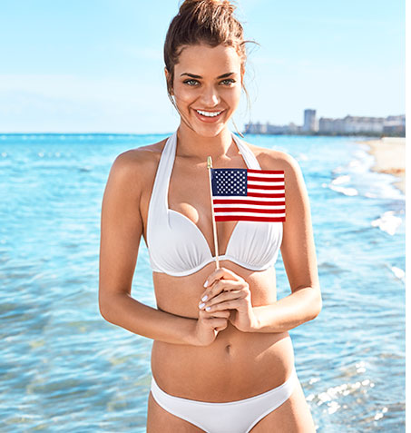 Woman, standing on the beach holding an American flag, wearing a white push-up bikini top and matching bottoms.